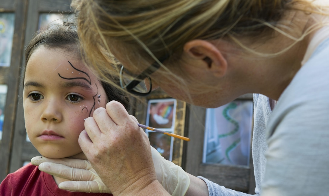 A child sits to have her face painted during the Ramstein and Vogelweh Community Center's Olympic Family Night Aug. 22, 2016 at Ramstein Air Base, Germany. Along with face painting, children were able to compete in six events to receive a medal. (U.S. Air Force photo/Senior Airman Tryphena Mayhugh)