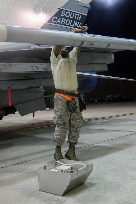 """Senior Airman Rick Ingram, South Carolina Air National Guard 169th Aircraft Maintenance Squadron weapons crew member, removes fins off an AIM-120 advanced medium-range air-to-air missile during exercise Beverly Herd 16-2 at Osan Air Base, Republic of Korea. Beverly Herd 16-2 is designed to test the readiness of Osan to be """"Ready to Fight Tonight."""" (U.S. Air Force photo by Staff Sgt. Jonathan Steffen)"""