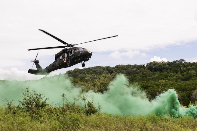 A medevac helicopter lands under green smoke marking a landing zone during an exportable combat training exercise at Fort Hood, Texas, Aug. 18, 2016. The exercise gives guardsmen an experience similar to a combat training center, but uses a nearby station to minimize cost. Army photo by Sgt. 1st Class Thomas Wheeler