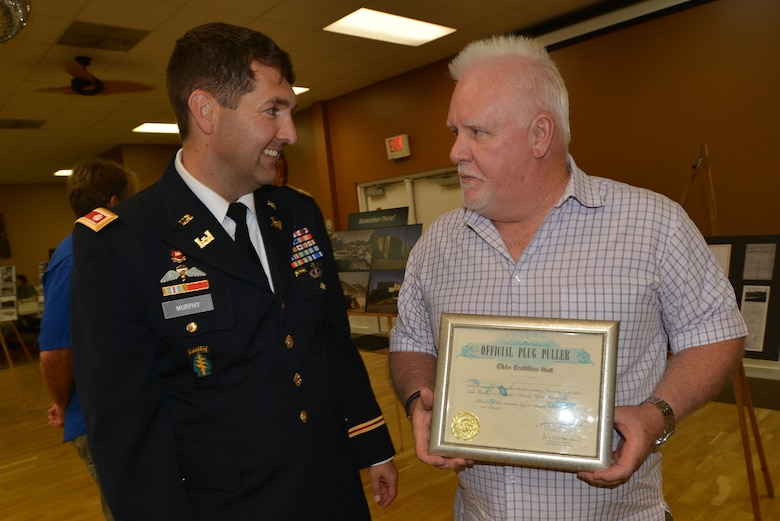 """Mike O'Leary (Right) shares an """"Official Plug Puller"""" certificate given to his father Bob at the dedication of Barkley Dam 50 years ago with Lt. Col. Stephen Murphy, U.S. Army Corps of Engineers Nashville District commander, during the reception following the commemoration marking the 50th anniversary of Barkley Dam Aug. 20, 2016. Mike and his dad rode through the lock and Barkley Canal."""