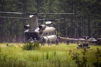 Paratroopers exit a CH-47 Chinook helicopter and unhook an M777A2 howitzer before participating in a gun raid and live-fire exercise at Fort Bragg, N.C., Aug 12, 2016. Army photo by Capt. Adan Cazarez