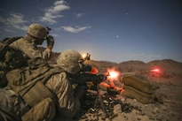 Marine Corps Lance Cpl. Login Loftis fires an M240 medium machine gun as Lance Cpl. Krikland Harrington looks through a night-vision device during Integrated Training Exercise 5-16 at Marine Air-Ground Combat Center in Twentynine Palms Calif., Aug. 18, 2016. The exercise brings together the ground, air and logistics combat elements of the Marine Corps into one unit ready to respond to global uncertainty. Marine Corps photo by Cpl. Timothy Valero