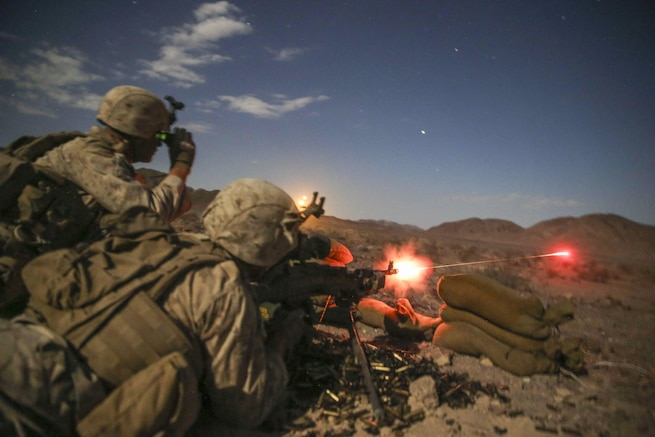 Marine Corps Lance Cpl. Login Loftis fires an M240 medium machine gun as Lance Cpl. Krikland Harrington looks through a night-vision device during Integrated Training Exercise 5-16 at Marine Air-Ground Combat Center in Twentynine Palms Calif., Aug. 18, 2016. Marine Corps photo by Cpl. Timothy Valero