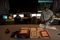 Col. Keith Green, the 618th Tanker Airlift Control Center director of operations, updates a classified binder at Scott Air Force Base, Ill., Aug. 1, 2016. Ongoing work by the Air Force and Army has filled training schedules by streamlining the Joint Airborne/Air Transportability Training program, an online system used by military units to request air support. (U.S. Air Force photo/Master Sgt. Brian Ferguson)