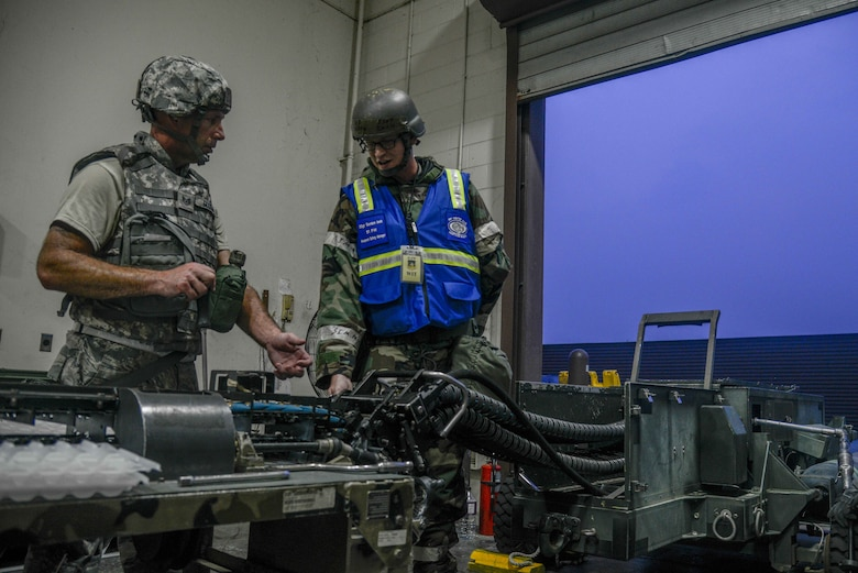 Tech. Sgt. Tony Goodwin, 51st Munitions Squadron conventional maintenance section chief, and Staff Sgt. Gordon Inch, 51st Fighter Wing weapons safety manager, troubleshoot an ammunition loading machine during Exercise Beverly Herd 16-2 at Osan Air Base, Republic of Korea, Aug. 23, 2016. Inch and 51st FW safety Airmen go out to various shops across Osan to ensure compliance and provide assistance and advice with safety concerns. (U.S. Air Force photo by Senior Airman Dillian Bamman)