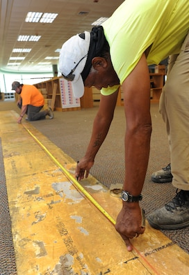 Layton Gipson and Ervin Morgan, Specialty Contractors and Associates, Inc. laborers, take measurements before  installing framing at the McBride Commons Aug. 22, 2016, on Keesler Air Force Base, Miss. The renovation will include a children's library, computer stations, engraving, framing, marketing and print shops and a full kitchen. The nine-month-long project is expected to be completed by May 2017. (U.S. Air Force photo by Kemberly Groue/Released)