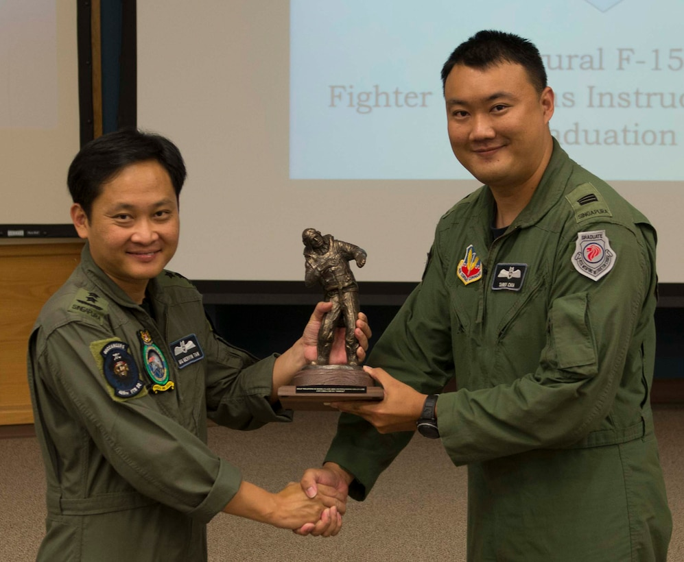 Republic of Singapore Air Force Maj. Gen. Mervyn Tan (left), Chief of RSAF, presents the top graduate award to Capt. Chia Chi Yu, 428th Fighter Squadron weapons systems officer, Aug. 19, 2016, at Mountain Home Air Force Base, Idaho. This was the first F-15SG Weapons Instructor course, designed to teach RSAF aircrew advanced combat maneuvers and tactics. (U.S. Air Force photo by Airman 1st Class Chester Mientkiewicz/Released)