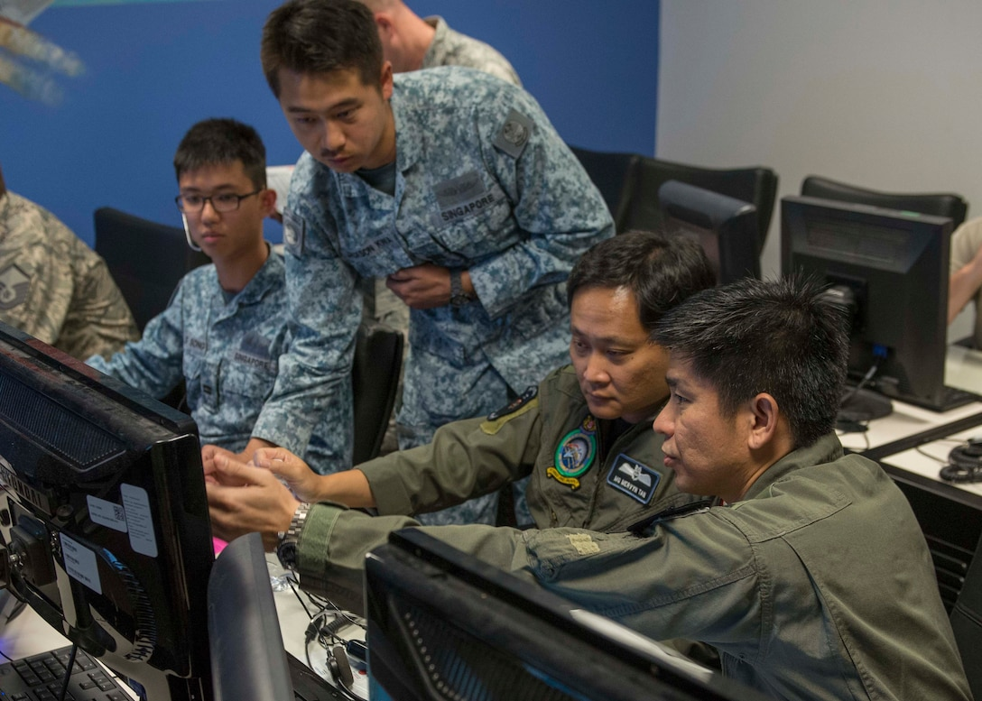 Republic of Singapore Capt. Jackson Kwa, 428th Fighter Squadron ground control intercept, shows an air-to-air dog fight to Major General Mervyn Tan, Chief of RSAF, and Brigadier General Tommy Tan Ah Han, RSAF Air Combat Command commander, Aug. 18, 2016, at Mountain Home Air Force Base, Idaho. The leaders visited different locations around base to experience the working relationship between the 428th FS and the rest of the Gunfighters. (U.S. Air Force photo by Airman 1st Class Chester Mientkiewicz/Released)