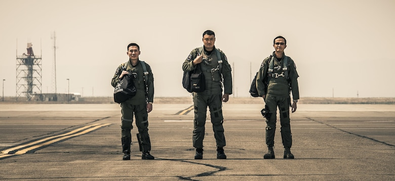 From the left, Republic of Singapore Air Force Weapons Systems Officers Capt. Alex Ong and Capt. Chia Chi Yu and F-15SG Pilot Maj. Wang Kee Yong stand on the flightline at Mountain Home Air Force Base, Idaho. The three are the first to graduate the RSAF Fighter Weapons Instructor Course, modeled after the U.S. Air Force Fighter Weapons School program. (U.S. Air Force photo by Senior Airman Lauren-Taylor Levin)
