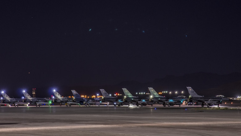 An F-16C Fighting Falcon from the 64th Aggressor Squadron, Nellis Air Force Base, Nev., awaits permission to take off on a taxiway between three F‐16Cs from the 5th Squadron, Rafiqui AFB, Pakistan, and four U.S. F-16CMs from the 55th Fighter Squadron, Shaw AFB, S.C., during a night sortie at Nellis AFB, Aug. 17, 2016. Red Flag 16-4 took place Aug. 15 - Aug. 26 and involved players from every branch of service as well as multiple nations. (U. S. Air Force photo by Tech. Sgt. Frank Miller)