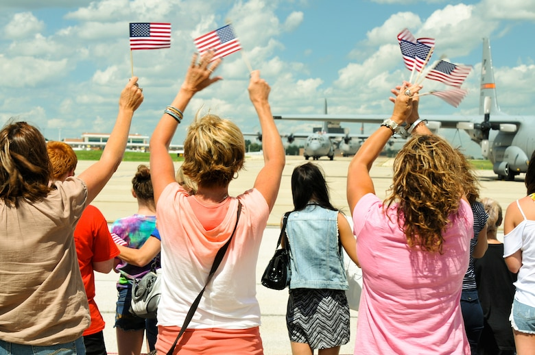 Friends and family of deployed unit members wave America flags as two C-130 Hercules aircraft taxi onto the 182nd Airlift Wing in Peoria, Ill., July 8, 2014. About 40 182nd aircrew and maintainers returned home from a deployment to Southwest Asia. They participated in Operation Enduring Freedom while assigned to the 379th Air Expeditionary Wing. (U.S. Air National Guard photo by Staff Sgt. Lealan Buehrer/Released)