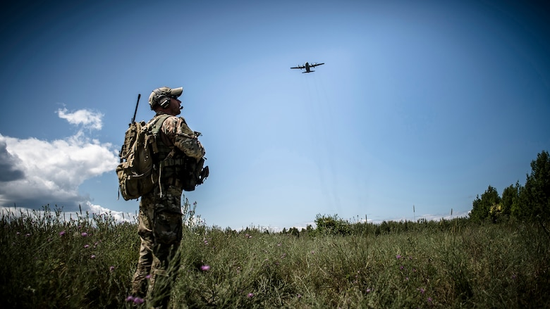 Polish armed forces joint terminal attack controller coordinate a resupply airdrop with a C-130 Hercules on an ambush training situation on July 21, 2015, with the 233rd Military Police Company, Springfield, Ill., provide security at Rogers City, Mich., during Exercise Northern Strike 2015. Exercise Northern Strike 2015 is a joint multi-national combined arms training exercise conducted in Michigan. (U.S. Air National Guard photo by Master Sgt. Scott Thompson/released)
