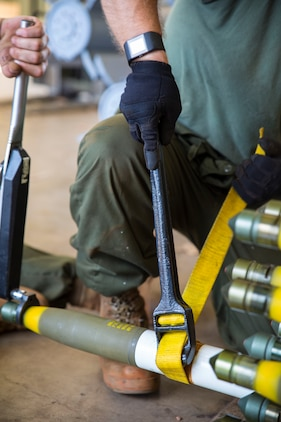 Marine Aviation Logistics Squadron (MALS) 12 Marines tighten a warhead onto a rocket during Southern Frontier at Royal Australian Air Force Base Tindal, Australia, Aug. 23, 2016. These ordnance Marines are working to meet Marine Fighter Attack Squadron (VMFA) 122's goal of dropping 138 tons of ordnance during Southern Frontier. The unit level training afforded Iwakuni Marines the opportunity to train with high explosive weapon body groups typically not used in Japan, while expanding technical and tactical proficiency in their craft. Munitions built during this training are in support of VMFA-122, who also gains experience and qualifications in low altitude, air-ground, high explosive ordnance delivery at the unit level. (U.S. Marine Corps photo by Cpl. Nicole Zurbrugg)
