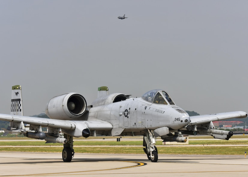 An A-10 Thunderbolt II, assigned to the 25th Fighter Squadron, taxis along the runway as an F-16 Fighting Falcon, assigned to the South Carolina Air National Guard 169th Fighter Wing, takes off during Exercise Beverly Herd 16-2 at Osan Air Base, Republic of Korea, Aug. 24, 2016. The two airframes were used to fly multiple sorties in support of the exercise, providing both pilots, maintenance and munitions Airmen the chance to hone their quick-turnaround skills. (U.S. Air Force photo by Senior Airman Victor J. Caputo)