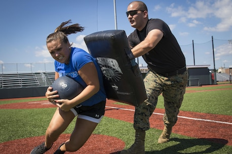 U.S. Marine Corps Sgt. Phillip Voss, a canvassing recruiter with Recruiting Substation North Boston, blocks a University of Massachusetts - Boston women's soccer team player from completing an obstacle during a leadership seminar at the UMass Boston fields, Aug. 19. Marine Corps leadership seminars are events wherein participants are taught about what makes good individual leaders and team cohesiveness followed by a workout regimen designed to make participants exercise those leadership principles under stress.
