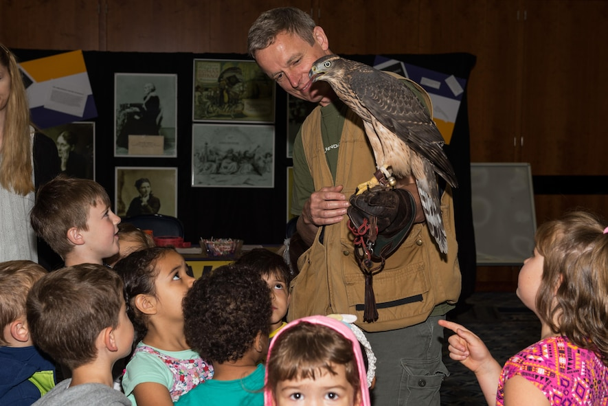 Jens Fleer, base falconer, Spangdahlem Air Base, Germany, introduces his falcon to a group of children from Kindergarten Spangdahlem, city of Spangdahlem, Germany, during Multicultural Awareness Day Aug. 18, 2016 at Club Eifel on base. Approximately 2,000 people attended the multicultural awareness event. (U.S. Air Force photo by Tech. Sgt. Amanda Currier)