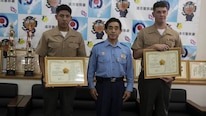 Lance Cpl. Luis Rosas, left, and Cpl. Ian Burnham, right, are presented a letter of appreciation by Eikatsu Sakihara, the Chief of the Urasoe City Police Department at the Urasoe City Police Department, Okinawa, Japan, Aug. 23, 2016. Rosas and Burnham were awarded for their efforts in assisting an Okinawa resident from a burning vehicle, and eliminating hazards at the scene of a car crash on April 16. Rosas is a Wilmington, Calif. native, and an engineer equipment mechanic with Combat Logistics Regiment-35, 3rd Maintenance Bn., 3rd Marine Logistics Group, III Marine Expeditionary Force. Burnham is a Spokane, Washington native, and electrical engineer equipment systems technician with CLR-35, 3rd Maintenance Bn., 3rd MLG, III MEF.