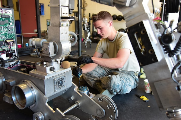 Senior Airman Nicholas Stewart, 21st Civil Engineer Squadron explosive ordnance disposal technician, applies lubricant to an actuator part of an Northrop Grumman Remotec's ANDROS F6A EOD robot during a maintenance class at Peterson Air Force Base, Colo., Aug. 17, 2016. The 21st EOD leadership tries to arrange this training for their Airman every two to three years to make sure they are fully capable of performing any trouble shooting that might be necessary. (U.S. Air Force photo by Staff Sgt. Amber Grimm)