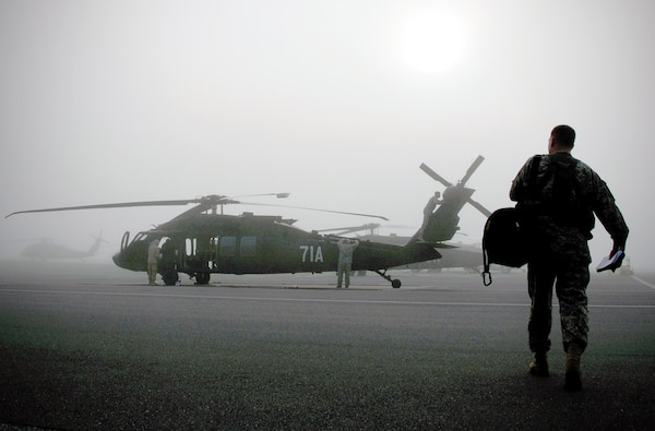 An instructor pilot walks onto the flightline while maintenance crews inspect at UH-60M Black Hawk helicopter at Lowe Army Heliport, Fort Rucker, Ala. in a dense fog that blanketed lower part of the state for several hours on the morning of May 9, 2013. Maintenance of existing equipment is crucial to keeping operating costs low for the multi-functional aircraft that has been used around the world for the past three decades. (U.S. Army photo by Sgt. 1st Class Andrew Kosterman/Fort Rucker public affairs).