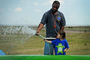 Maj. Merrell Mobley, 50th Force Support Squadron commander, helps Madie Janaros soak sliders during Slide the City at Schriever Air Force Base, Colorado, Friday, Aug. 19, 2016. Mobley was one of the more than 20 Team Schriever members who volunteered to man the slide during the event. (U.S. Air Force photo/Katie Calvert)