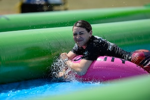 Kelly Caggiano tubes down a giant slip-and-slide during Slide the City at Schriever Air Force Base, Colorado, Friday, Aug. 19, 2016. The 50th Force Support Squadron brought the popular event back to the base for a second straight year as part of the squadron's continued efforts to improve the quality of life for Team Schriever and their families. (U.S. Air Force photo/Christopher DeWitt)