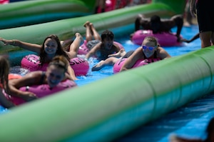 Participants slide down a giant slip-and-slide during Slide the City at Schriever Air Force Base, Colorado, Friday, Aug. 19, 2016. Slide the City returned to Schriever for a second straight year, for Team Schriever and local community members to enjoy. (U.S. Air Force photo/Christopher DeWitt)