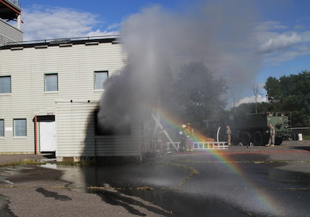 FORT MCCOY, Wis. – Water, smoke and soot spew from a window after U.S. Army Reserve firefighters from the 237th Firefighter Detachment, Sturtevant, Wis., vent the room in the burn house following suppressing a fire during an exercise at Fort McCoy, Aug. 21, 2016. The training helped firefighters find weaknesses in their techniques, while learning new ones. (U.S. Army Reserve Photo by Sgt. Quentin Johnson, 211th Mobile Public Affairs Detachment/Released)