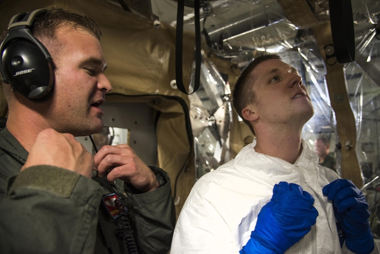 Staff Sgt. Branden Beers, 375th Aeromedical Evacuation Squadron aeromedical evacuation technician, instructs Capt. Micheal Broome 375th AES flight nurse, on how to take off his paper suit while exiting a Transportation Isolation System used for training, Aug. 18, 2016. The TIS is used to transport sick and contagious patients to more definitive care without compromising the safety of the crew. (U.S. Air Force Photo by Airman Daniel Garcia)