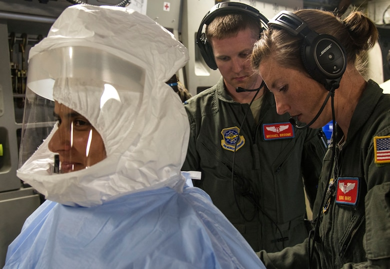 Captains Micheal Broome and Nicole Ward, 375th Aeromedical Evacuation Squadron flight nurses, prepare Capt. Andrea De Oliveira, 375th AES flight nurse to enter a Transportation Isolation System for training, Aug. 18, 2016. The TIS is used to transport sick and contagious patients to more definitive care without compromising the safety of the crew. (U.S. Air Force Photo by Airman Daniel Garcia)