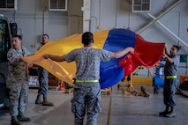 Airmen from the United States and Colombian Air Forces prepare a flag for display during Exercise Green Flag East at Barksdale Air Force Base, La., Aug. 15, 2016. Green Flag East provides pilots with simulated scenarios to train in a high-threat environment, and affords maintenance and support personnel an increased tempo in generating fully mission-capable combat aircraft. (U.S. Air Force photo/Senior Airman Mozer O. Da Cunha)