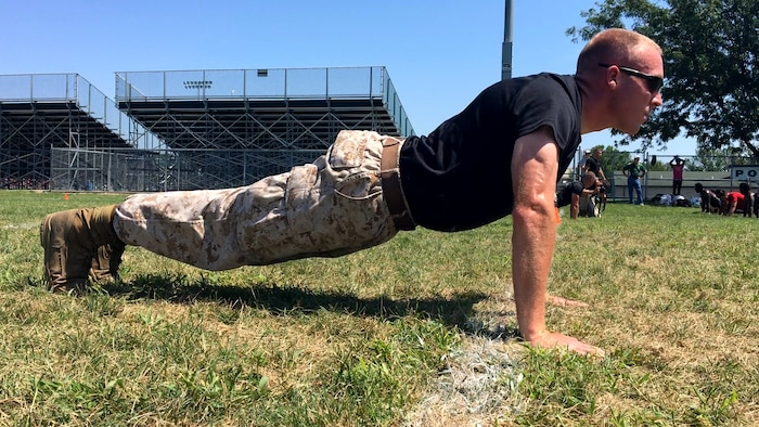 Sgt. Joseph E. Fralix, a recruiter for Recruiting Sub Station Des Moines, pushes off the ground during a push-up challenge at the Football Leadership Camp at North High School Grubb Stadium, Aug. 18. Fralix staring straight forward demonstrates bearing, one of the 14 leadership traits in the Marine Corps. (U.S. Marine Corps photo by Cpl. Jennifer Webster/Released)