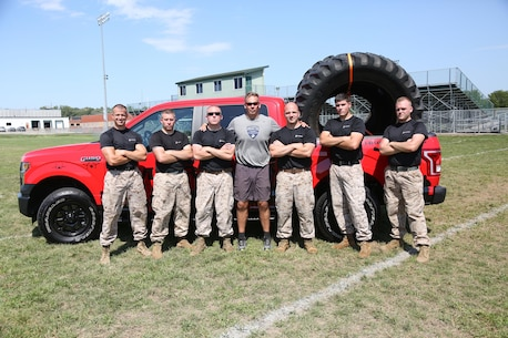 Marines from Recruiting Station Des Moines pose at the Football Leadership Camp at North High School Grubb Stadium, Aug. 18. Listed from left to right: Staff Sgt. Kaleb V. Wagy, Staff Sgt. Michael T. Huck, Sgt. Joseph E. Fralix, retired Maj. Sean Quinlan, Cpl. Brock T. Gaul and Cpl. Buray T. Kiser. (U.S. Marine Corps photo by Cpl. Jennifer Webster/Released)