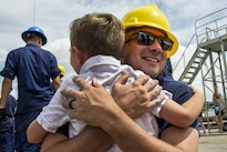 Coast Guard Petty Officer 1st Class Justin Pearl reunites with his family after arriving on the Barque Eagle at the Coast Guard Yard in Baltimore, Aug. 19, 2016. The Eagle departed the Yard in April for port calls in Europe, Bermuda, and the eastern United States to carry out its mission to train future Coast Guard officers. Coast Guard photo by Petty Officer 2nd Class Lisa Ferdinando