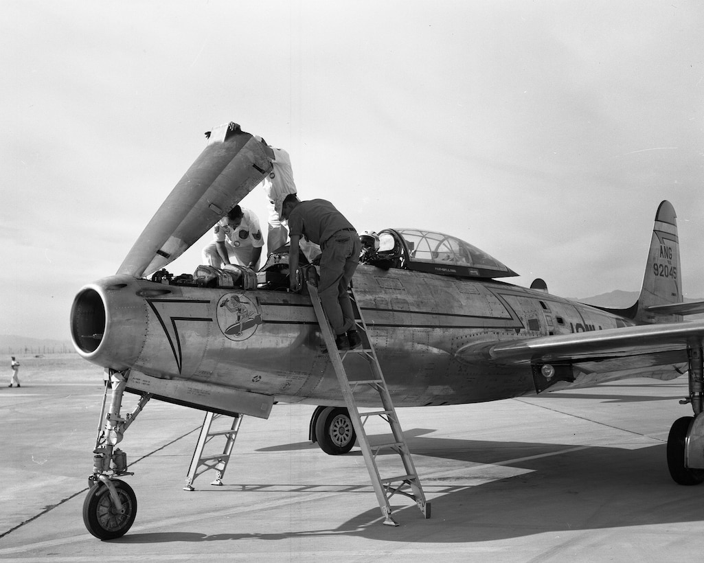 Ground crew load munitions on a U.S. Air Force F-84E Thunderjet assigned to the Iowa Air National guard while at the Air National Guard gunnery completion in 1956. As a component of the 132nd Fighter Interceptor Wing the 174th Fighter Interceptor Squadron in Sioux City flew the F-84 until 1958. During that time the 174th was awarded the Spaatz Trophy as the most outstanding Air National Guard squadron in the nation.