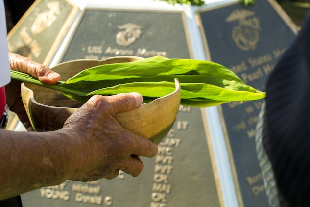 Minister Kahu Kelekona Bishaw performs a traditional Hawaiian blessing during the Marine Memorial Rededication Ceremony at the USS ARIZONA Education Center, Honolulu, Hawaii, Aug. 19, 2016.  The significance of the blessing is that fresh Hawaiian water is always used to represent rebirth and the maile lei, the plant, for continued growth and prosperity.