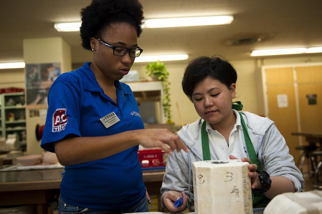 Haruka Fukuchi, 18th Force Support Squadron intern, learns how to make clay sculptures from Miracle Williams, 18th FSS recreational aid Aug. 24, 2016, at Kadena Air Base, Japan. On top of refining their English skills, KLI interns learn new skills and create new friendships with Airmen and American civilians alike. (U.S. Air Force photo by Airman 1st Class Corey M. Pettis)