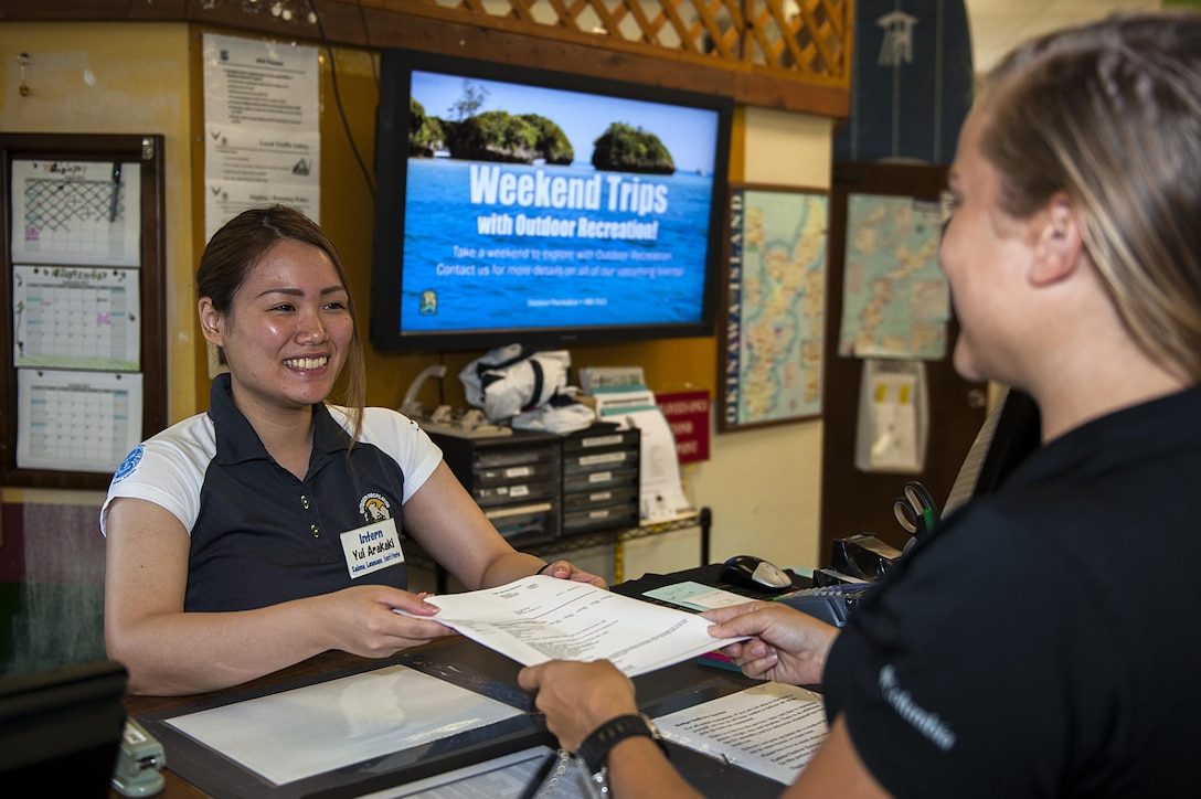 Yui Arakaki, 18th Force Support Squadron intern, hands an informational packet to a customer Aug. 24, 2016, at Kadena Air Base, Japan. KLI interns have the opportunity to build ties between Kadena and the community while practicing their English skills. (U.S. Air Force photo by Airman 1st Class Corey M. Pettis)