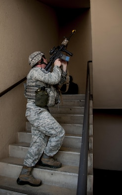 Master Sgt. Tim Shaw, 51st Security Forces flight chief, clears stairs during a mock attack on the 51st Communications Squadron building at Osan Air Base, Republic of Korea, Aug. 25, 2016. The mock attack allowed 51st CS Airmen to practice their base defense techniques procedures. (U.S. Air Force photo by Staff Sgt. Jonathan Steffen)