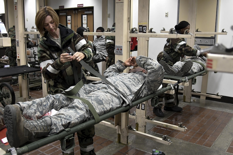 Medics from the 51st Medical Group secure mock patients to a stretcher prior to aeromedical evacuation during Exercise Beverly Herd 16-2 on Osan Air Base, Republic of Korea, Aug. 24, 2016. The patients will be evacuated to a facility that can handle their needs and to relieve stress from Osan's medical treatment facility. (U.S. Air Force photo by Staff Sgt. Jonathan Steffen)