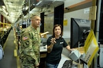 Kandi Foy, shipping and receiving clerk at DLA Distribution Hill, Utah, is demonstrating the Distribution Standard System to Army Brig. Gen. John Laskodi, DLA Distribution commander, during his visit on Aug. 17.  Foy is showing how she performs the pick and stow functions in the Automated Storage Module.
