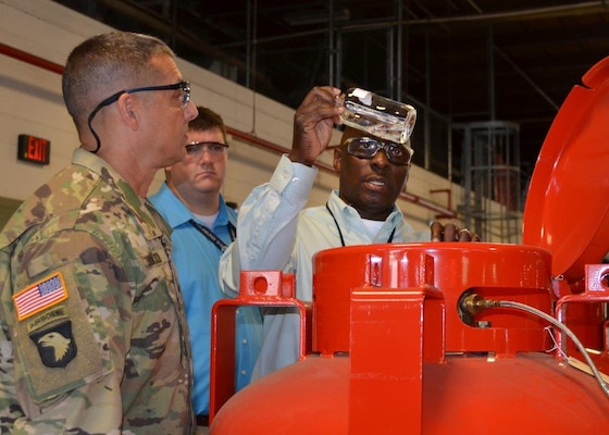 Anthony Whiteside, DLA Distribution Richmond ODS supervisor, explains how visual sample analysis of Halon are done to Army Brig. Gen. John Laskodi, DLA Distribution commander, during his visit to the distribution center on Aug. 12.