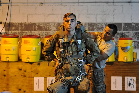 U.S. Army soldiers assigned to the 3rd Brigade Combat Team, 82nd Airborne Division from Fort Bragg, N.C., demonstrates fastening procedures for parachutes prior to a mass personnel drop Aug. 18, 2016, near Fort Polk, La. The jump provides realistic training for soldiers to prepare for contingency operations and marks the beginning of Exercise Green Flag Little Rock 16-09.  (U.S. Air Force photo by Airman Kevin Sommer Giron)