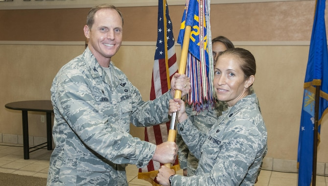 Lt. Col. Nicole Capozzi accepts the 682d Air Support Operations Squadron guidon from Col. Chris Jensen, 18th Air Support Operations Group commander, during a change-of-command ceremony at the group here July 22. Capozzi took command of the 682d ASOS from Lt. Col. David Arriola, who had commanded the unit since July 2014. (U.S. Air Force photo/Marc Barnes)