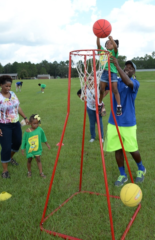 A young child receives assistance while playing basketball after Marine Corps Logistics Base Albany's Summer Reading Awards Program at Covella Pond, Aug. 20.