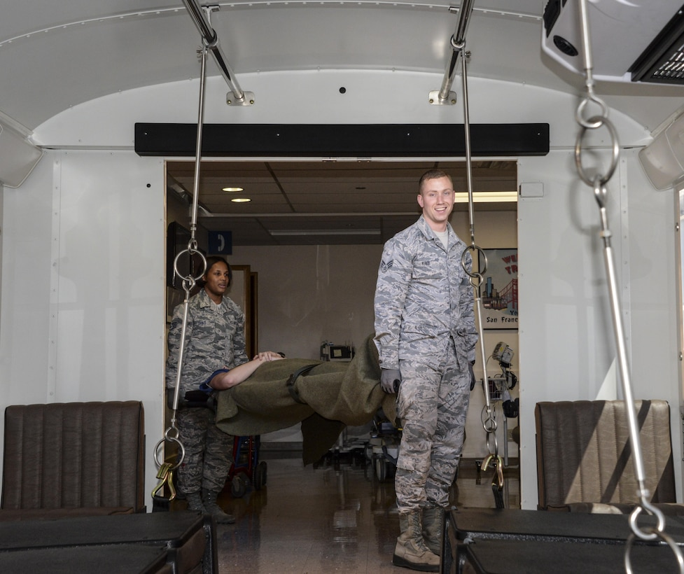 Senior Airman Adam King and Staff Sgt. Katrevious Swift, 60th IPTS health service management technicians, load a patient onto an ambus Aug. 23 at Travis Air Force Base, Calif. The En-route Patient Staging Facility Flight provides support and continues medical care for patients coming in from or going out to an aircraft.