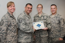 Master Sgt. Nicholas Souza, center, Air Force Life Cycle Management Center Detachment 7 first sergeant, presents the Diamond Sharp Award to Staff Sgt. Autumn Bogert, Battle Management NCO in charge Operations Management, in Building 1624, Aug. 24, while Master Sgts. Jessica LaBrie, 66th Air Base Group first sergeant, and Richard Abbott, 66th Security Forces Squadron first sergeant, look on. The Diamond Sharp program, adopted by the First Sergeant Council, aims to recognize Airmen in the grades of airman basic through technical sergeant. (U.S. Air Force photo by Mark Herlihy)