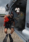 Navy Petty Officer Class Chris Nelson, crew chief, prepares to lower Navy Petty Officer 1st Class Harrison Greenmaki into the waterduring training at Naval Support Activity Panama City, Fla., Aug. 24, 2016. Greenmaki is a search and rescue swimmer. Navy photo by Petty Officer 2nd Class Fred Gray IV