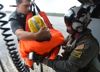 Navy Petty Officer 1st Class Harrison Greenmaki, left, and Petty Officer 1st Class Chris Nelson bring the rescued dummy into the helicopter at Naval Support Activity Panama City, Aug. 24, 2016. Navy photo by Petty Officer 2nd Class Fred Gray IV