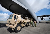 U.S. and Canadian soldiers discuss different techniques and methods for uploading vehicles onto an Canadian air force Globemaster III aircraft in Greenville, S.C., Aug. 13, 2016. Army National Guard photo by Staff Sgt. Roby Di Giovine