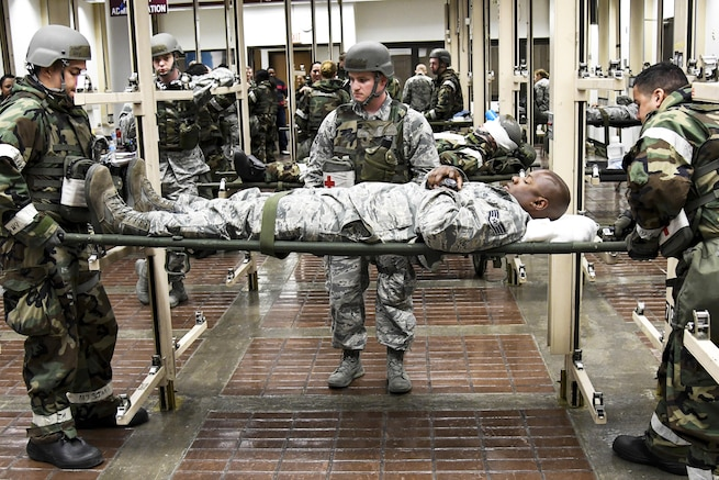 Airmen transport a mock patient to a stretcher in an aeromedical evacuation training scenario during Exercise Beverly Herd 16 on Osan Air Base, South Korea, Aug. 24, 2016. The training allows medics to hone their skills to safely transport patients to aircraft. Air Force photo by Staff Sgt. Jonathan Steffen